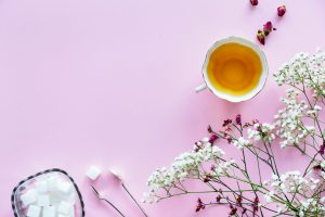 A cup of valerian tea on a pink background surrounded by flowers.
