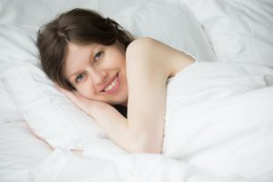 smiling woman lying in bed with a denver mattress