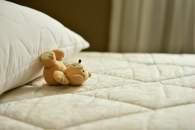 a small teddy bear on top of a bed