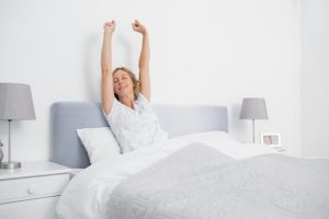 woman woke up on a Tempurpedic Mattress Topper and had a nice sleep on it