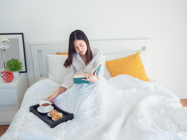 woman in bed with book and tea