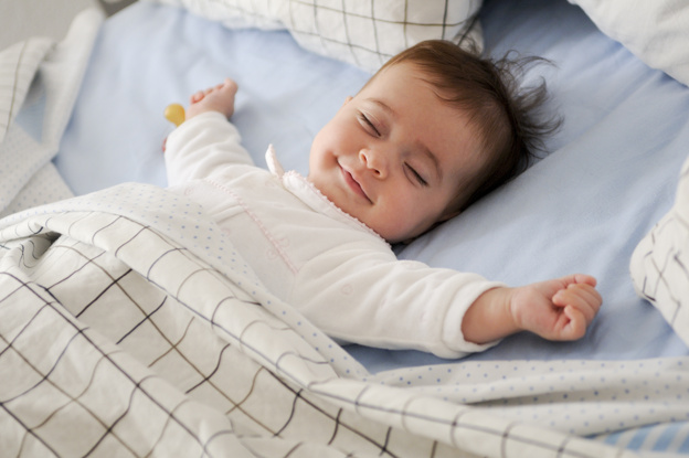 Smiling baby girl lying on a bed sleeping on bed